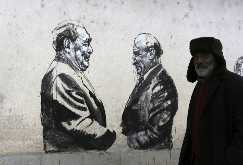 Nikolay, resident of the Staro Zhelezare passes in front of  a mural depicting Russian and Bulgarian leaders Leonid  Brezhnev, left,  and  Todor Zhivkov facing each other in the Bulgarian village of Staro Zhelezare on Wednesday, Jan. 27, 2016. The sleepy village of Staro Zhelezare  in central Bulgaria is harnessing the power of celebrities, hoping for an economic revival through art.  Outdoor murals in the village feature local people alongside celebrities on their homes. Homeowners are depicted with personalities such as Pope Francis, Queen Elizabeth II, Angela Merkel, Indira Gandhi, Margaret Thatcher, Barack Obama and Fidel Castro.  (AP Photo/Valentina Petrova)