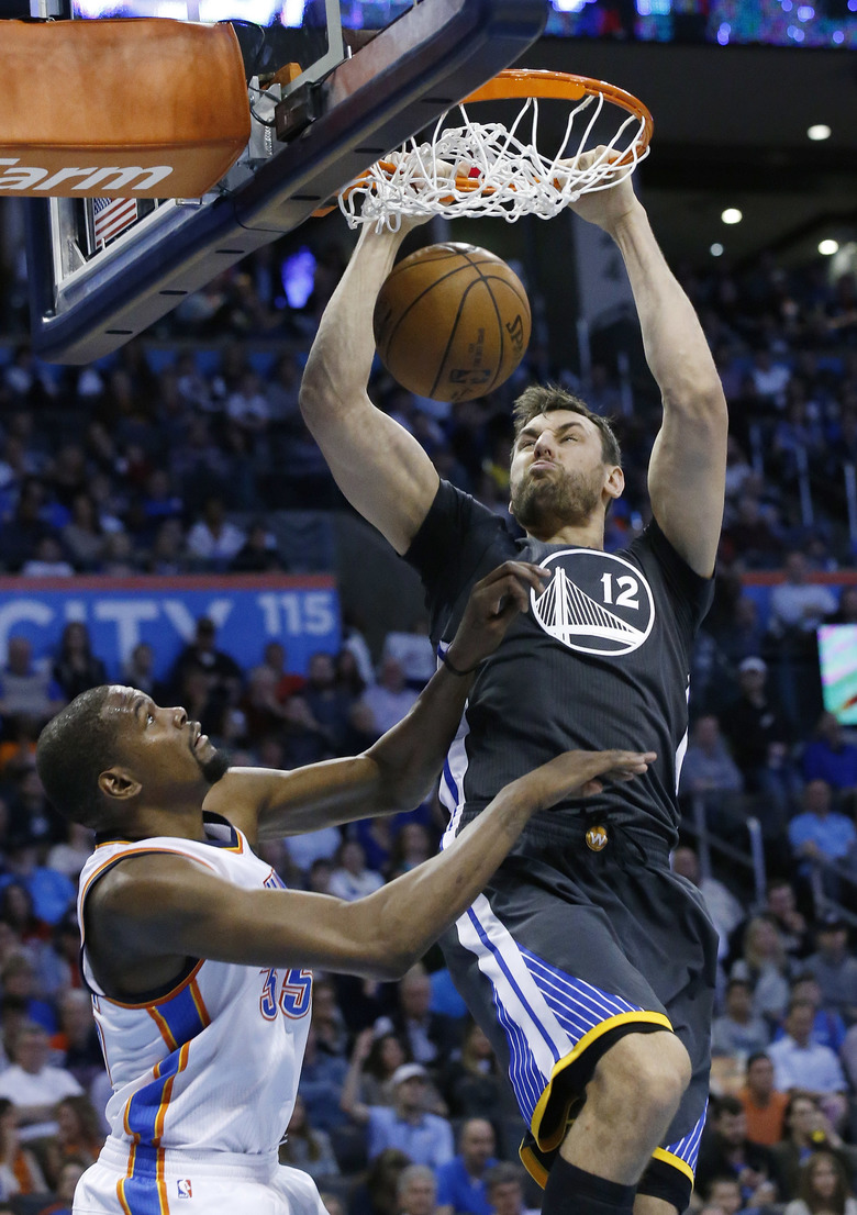 Golden State Warriors center Andrew Bogut (12) dunks in front of Oklahoma City Thunder forward Kevin Durant (35) during the second quarter of an NBA basketball game in Oklahoma City, Saturday, Feb. 27, 2016. (AP Photo/Sue Ogrocki)