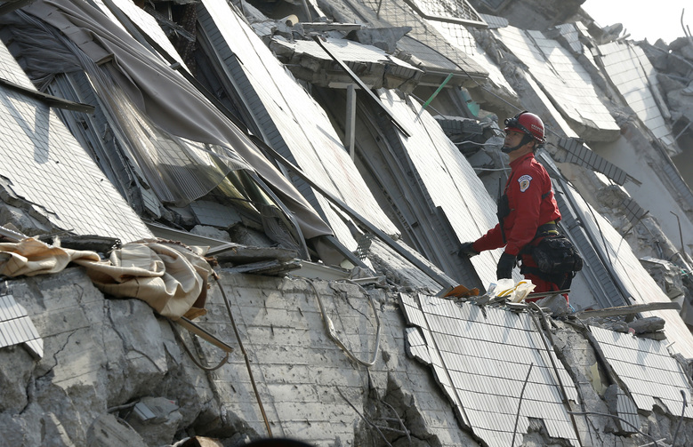 An emergency rescue team member searches for the missing in a collapsed building from an earthquake in Tainan, Taiwan, Sunday, Feb. 7, 2016. Rescuers on Sunday found signs of live within the remains of the high-rise residential building that collapsed in a powerful, shallow earthquake in southern Taiwan that killed over a dozen people and injured hundreds. (AP Photo/Wally Santana)