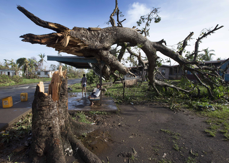 Two boys are under a bus shelter that is supporting a fallen tree in the village of Talecake, Fiji, Wednesday, Feb. 24, 2016, after cyclone Winston ripped through the island nation. The cyclone tore through Fiji over the weekend with winds that reached 177 miles (285 kilometers) per hour, making it the strongest storm in Fiji's recorded history. (Brett Phibbs/New Zealand Herald via AP) NEW ZEALAND OUT, AUSTRALIA OUT