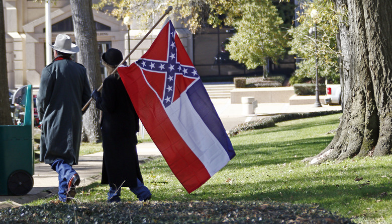 A couple leaves the grounds of the state Capitol in Jackson, Miss., after participating in a rally in support of keeping the Confederate battle emblem on the state flag. In Mississippi, the last state to display the Confederate battle emblem on its flag, some lawmakers want the divisive symbol removed, others want to punish public institutions that refuse to fly the banner and a state House leader suggests having two separate but equal flags: one with the rebel cross and one without.  (AP Photo/Rogelio V. Solis, File)