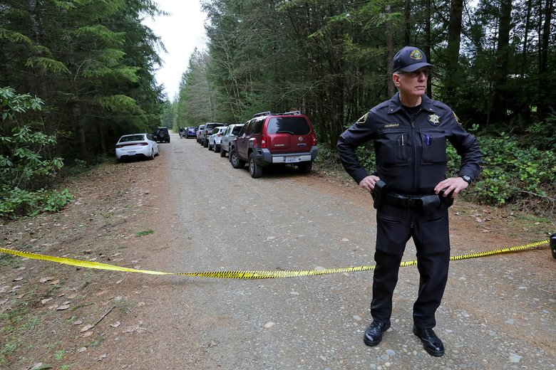 Mason County Deputy Chief Russell Osterhout stands near crime-scene tape blocking access to a rural property where four people were killed. The suspected gunman later took his own life. (Greg Gilbert/The Seattle Times)