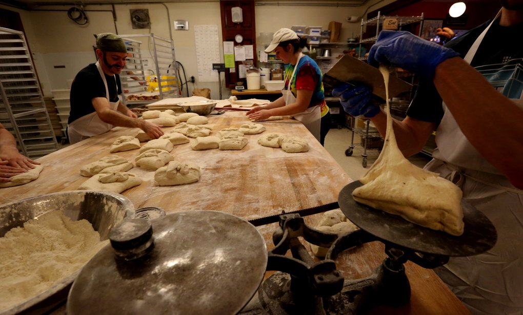 Dough is quickly weighed before forming into loaves.  (Alan Berner/The Seattle Times)
