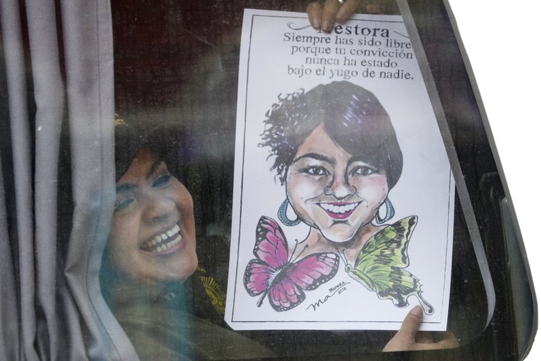 "Community police force leader Nestora Salgado, holds up a caricature of herself, as she is transported via bus from the Tepepan prison after courts threw out charges of homicide and kidnapping in Mexico City, Friday, March 18, 2016. Salgado, who has dual U.S. and Mexican citizenship, returned to Mexico in 2004 and joined one of the community police forces in Olinala, a town about 110 miles (180 kilometers) south of Mexico City. While legal, the community police forces have often had a troubled relationship with state and federal authorities. She was arrested in August 2013 after people who had been detained by the force filed a complaint of kidnapping. The Spanish text translates to; ""Nestora, You have always been free because your conviction has never been under the oppression of anybody."" (AP Photo/Marco Ugarte)"