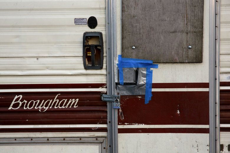 A resident keeps a lock on a  motorhome parked at a temporary RV camp in Magnolia's Interbay neighborhood on Feb. 8. (Erika Schultz / The Seattle Times)