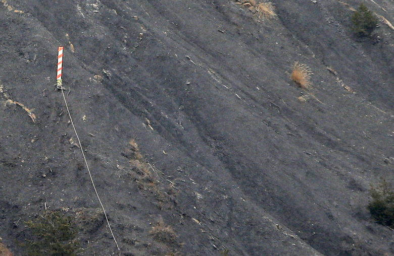 A marker is set up to show the Germanwings plane crash site near Seyne-les-Alpes, Wednesday, March 23, 2016. The families of the 150 passengers and crew killed in the March 24, 2015, crash are to attend on Thursday March 24,  a ceremony marking one year after the plane crash, in Le Vernet, French Alps. (AP Photo/Christophe Ena)