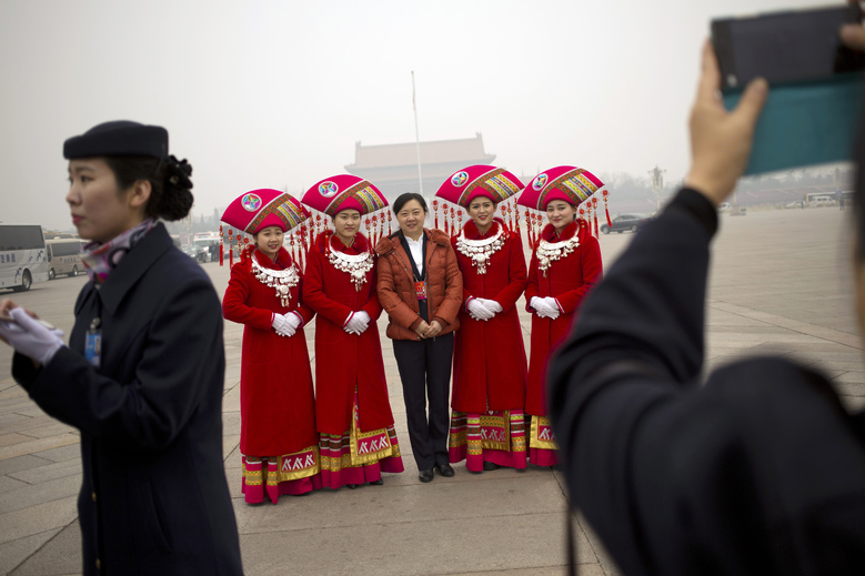 Hostesses, who facilitated the arrival of delegates by bus, pose for photos on Tiananmen Square near the Great Hall of the People in Beijing during a meeting ahead of Saturday's opening session of China's National People's Congress (NPC), Friday, March 4, 2016. The political conclave comes as China's leaders are being tested by new challenges including an economy that has slowed to a 25-year low, global uncertainty over the country's tumultuous stock markets and currency movements, and tensions over the South China Sea. (AP Photo/Mark Schiefelbein)