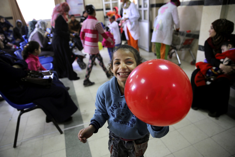In this Thursday, March 17, 2016 photo, a child laughs during the visit of Palestinian clown doctors, Majed Kaloub, and Alaa Miqdad, at the Al-Rantisi children's hospital in Gaza City. Majed and Alaa were not trained in hospital clowning, but they grew up in a place that saw three large-scale military conflicts between Israel and Gaza's Hamas rulers in the past decade, let alone dozens of smaller rounds of violence. Both visit three medical centers in the Gaza Strip a week and spend two days at Al-Rantisi, a specialized hospital for children with chronic illnesses. (AP Photo/Adel Hana)