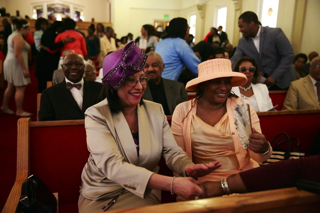 First lady Phyllis Gearring-Anderson, in purple hat, shakes hands with congregation members at First African Methodist Episcopal Church. (Erika Schultz/The Seattle Times)