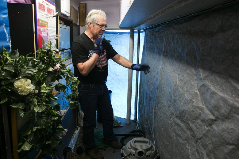 """Earl """"The Squirrel"""" Adams, buyer at Squirrel's Buy&Sell on North 85th Street in Greenwood, cleans up glass from their front window display case after a gas explosion leveled three businesses and damaged others in the Greenwood neighborhood of Seattle Thursday March 10, 2016. He said that when he heard the news, he feared for the life of a homeless man he often saw sleeping in the alley behind the businesses that were hit hardest. """"He must have gone somewhere else for the night,"""" he said. (Bettina Hansen/The Seattle Times)"""