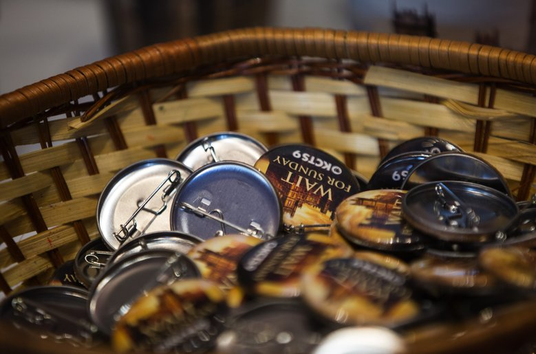 "Dozens of small ""Downton Abbey"" buttons sit in a basket for attendees to take.  (Lindsey Wasson/The Seattle Times)"