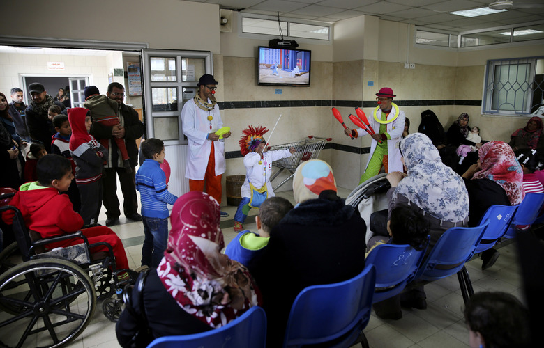 In this Thursday, March 17, 2016 photo, Palestinian clown doctors, 24-year-old Majed Kaloub, top center, and 33-year-old Alaa Miqdad, bottom center, perform for children during their visit at the Al-Rantisi children's hospital in Gaza City. Majed and Alaa were not trained in hospital clowning, but they grew up in a place that saw three large-scale military conflicts between Israel and Gaza's Hamas rulers in the past decade, let alone dozens of smaller rounds of violence. Both visit three medical centers in the Gaza Strip a week and spend two days at Al-Rantisi, a specialized hospital for children with chronic illnesses. (AP Photo/Adel Hana)