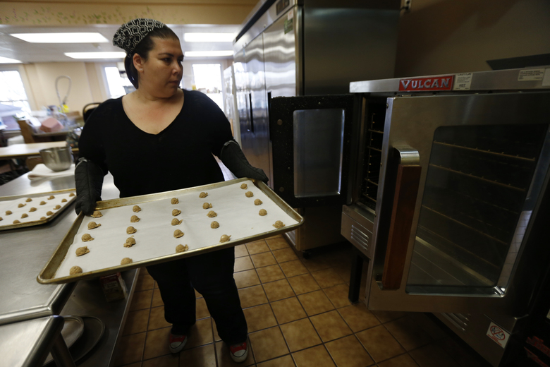 In a Thursday, March 10, 2016, photo, baker Martha Rabello works on making coffee cookies in the kitchen of Fanwood Presbyterian Church in Fanwood, N.J. Rabello rents space in the church's kitchen to bake her goods to sell, as a state law prohibits her from baking commercial goods in her home. A group of bakers have pushed for a bill that will allow them to bake at home and not in rented kitchen space. (AP Photo/Julio Cortez)