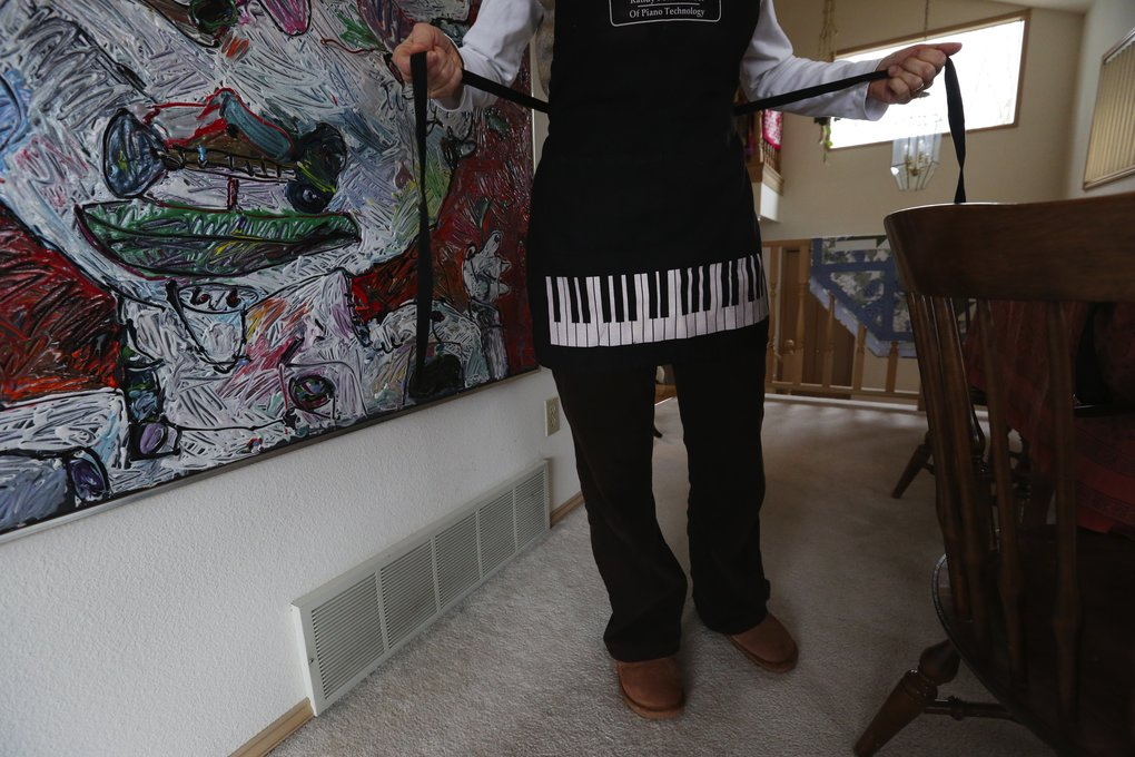 Appropriate to her profession, Ginny Bear, piano tuner, has an apron reflecting her craft. (Alan Berner/The Seattle Times)