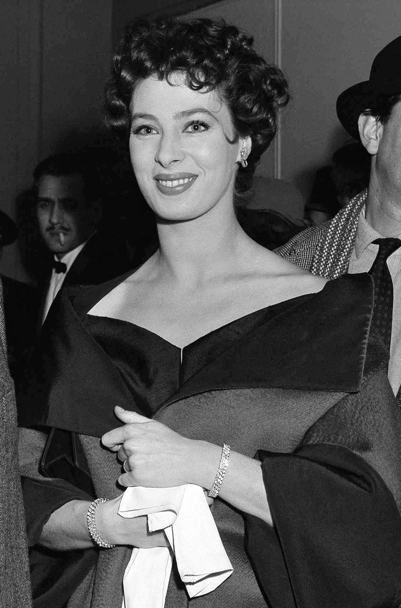 "FILE – In this March 4, 1954, file photo, actress Rita Gam stands in lobby of Longacre Theatre at opening of  ""The Burning Glass"" in New York. Gam, who had a lengthy acting career on film, television and stage, died Tuesday, March 22, 2016. She was 88. (AP Photo/Ed Ford, File)"