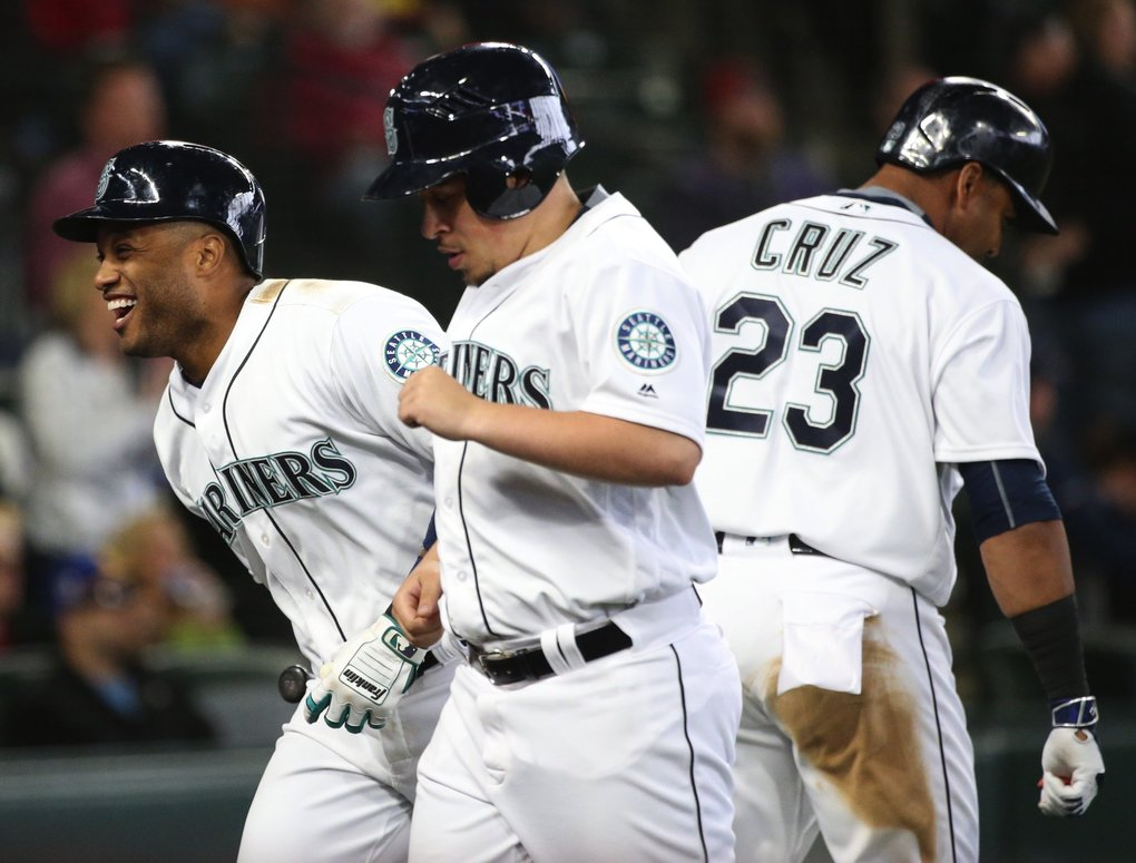 Approaching the dugout, Mariners second baseman Robinson Cano, left, is all smiles after knocking a home run in the fifth inning to give the M's a one run lead over Texas.   (Ken Lambert / The Seattle Times)