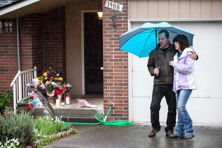 A couple views a small memorial on the porch of the Renton home of Ingrid Lyne, whose partial remains were found over the weekend in Seattle.   (Dean Rutz / The Seattle Times)