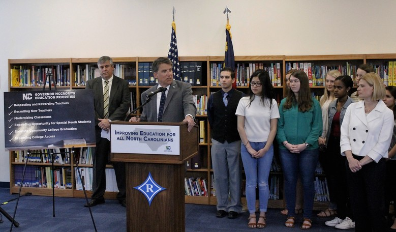 North Carolina Gov. Pat McCrory, flanked by students and a state official, discusses his education proposals for the state budget, Tuesday, April 5, 2016. McCrory appeared at Ragsdale High School in Jamestown, North Carolina, from which he graduated in 1974. (AP Photo/Skip Foreman)
