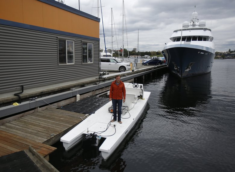 Andy Rebele, founder of Pure Watercraft, stands on a coach's launch, a boat popular among crew coaches. This boat is equipped with Pure Watercraft's low-profile electrical motor.  (Sy Bean/The Seattle Times)