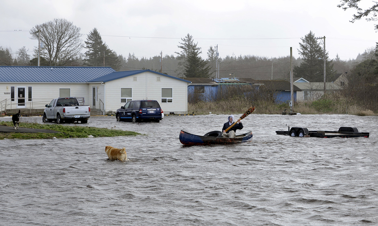 Quinault tribal member Sonny Curley canoes through Sea Breeze Field on the Quinault Reservation on March 10. The tribe is being forced to relocate part of the village of Taholah on the Washington coast due to ocean encroachment. (Larry Workman/Quinault Tribe)