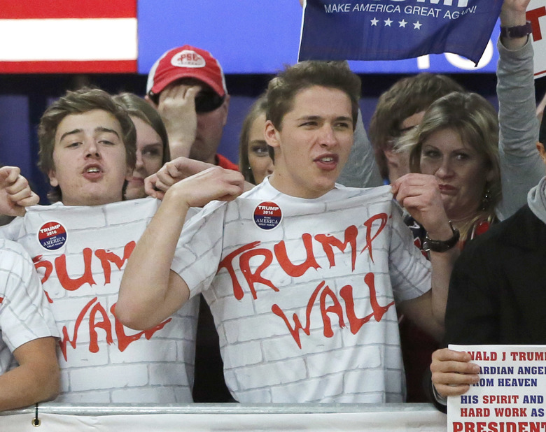 """FILE – In this Saturday, April 2, 2016 file photo, supporters of Republican presidential candidate Donald Trump chant, """"Build that wall,"""" before a town hall meeting in Rothschild, Wis. (AP Photo/Charles Rex Arbogast, File)"""