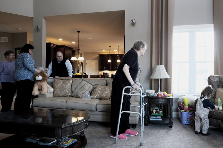 Terry Cadd walks over to her granddaughter, Josie Cadd, 2, while Barbara Spangler, left, her niece, Becky Cadd, and Cadd's husband, Jim, gather in their living room. (TJ KIRKPATRICK/NYT)