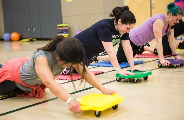 Marissa Scroggins, second from left, and others use small rollers for an ab exercise.  (Lindsey Wasson/The Seattle Times)