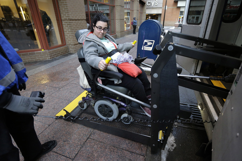 In this Tuesday, April 5, 2016 photo, Sarah Kaplan, of Lynn, Mass., rides an elevator to board a bus outside her place of work, in Boston. Transit systems in major U.S. cities are required by federal law to provide specialized services for disabled passengers. In Boston, the deficit-laden MBTA is considering ways of reducing service for the disabled and outsourcing more of it to taxis and ride-hailing services like Uber. (AP Photo/Steven Senne)