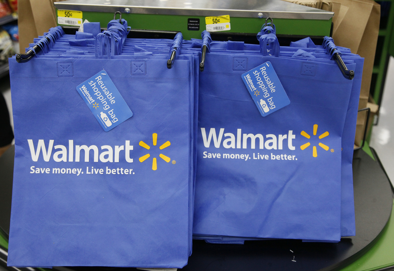 FILE – In this Thursday, Sept. 19, 2013, file photo, reusable shopping bags are offered for sale at a Wal-Mart Neighborhood Market, in the Chinatown district of Los Angeles. Wal-Mart is sharpening its attack against Amazon. The discounter says it is changing its membership-based free shipping service test to two days from three days and is charging one dollar less for the annual membership fee. Wal-Mart began testing the service in 2015 as a way to counter Amazon's highly successful Prime shipping. (AP Photo/Nick Ut, File)