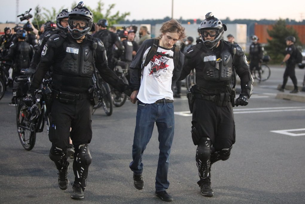 A protester is arrested in the parking lot of Costco on 4th Avenue South in Sodo. (Steve Ringman / The Seattle Times)