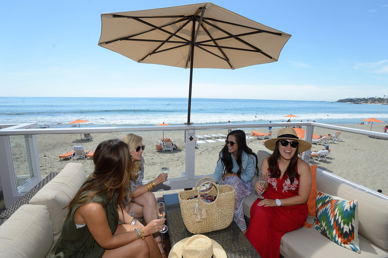 Fashion bloggers Kathleen Barnes, left, Niki Mencon, Lydia Webb and Miriam Gin, right, chat on the patio outside their beach-front bungalow at the Pacific Edge Hotel in Laguna Beach, Calif. (JEFF GRITCHEN/TNS)
