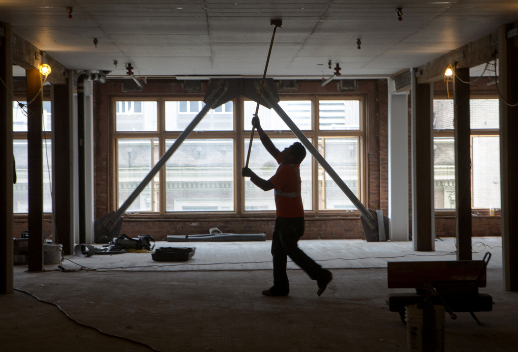 A construction worker finishes drywall at an old brick building on First Avenue being seismically retrofitted by Lake Union Partners. (Ellen M. Banner/The Seattle Times)