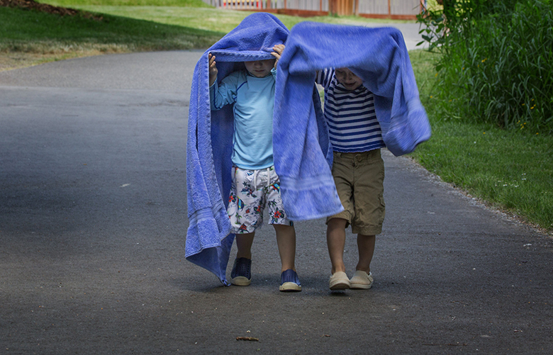 Miles Boike, 4 (left) and Rohan Velamoor, 3, peak out from under their towels to check out the path as they play being ghosts as they leave the beach at Luther Burbank Park on Mercer Island Friday afternoon, May 13, 2015, and head back to the car with their mothers and siblings (not in photo).  The boys' mothers have been dear friends for over 15 years.  Rohan lives on Mercer Island with his family.  Miles and his family will be moving there soon so Rohan's family was showing them all the sights on the island.
