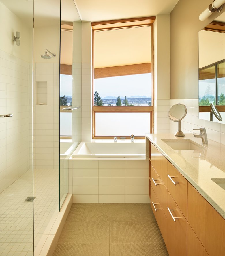 """In the mornings, I can see Mount Rainier,"" Mila says of the compact but efficient frameless glass shower. The Caesarstone countertop carries consistency and continuity from room to room. (Benjamin Benschneider/The Seattle Times)"