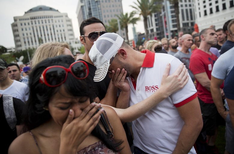 Mourners weep during the reading of the names of those killed in a mass shooting at the Pulse nightclub during a vigil downtown Monday, June 13, 2016, in Orlando, Fla. (AP Photo/David Goldman)