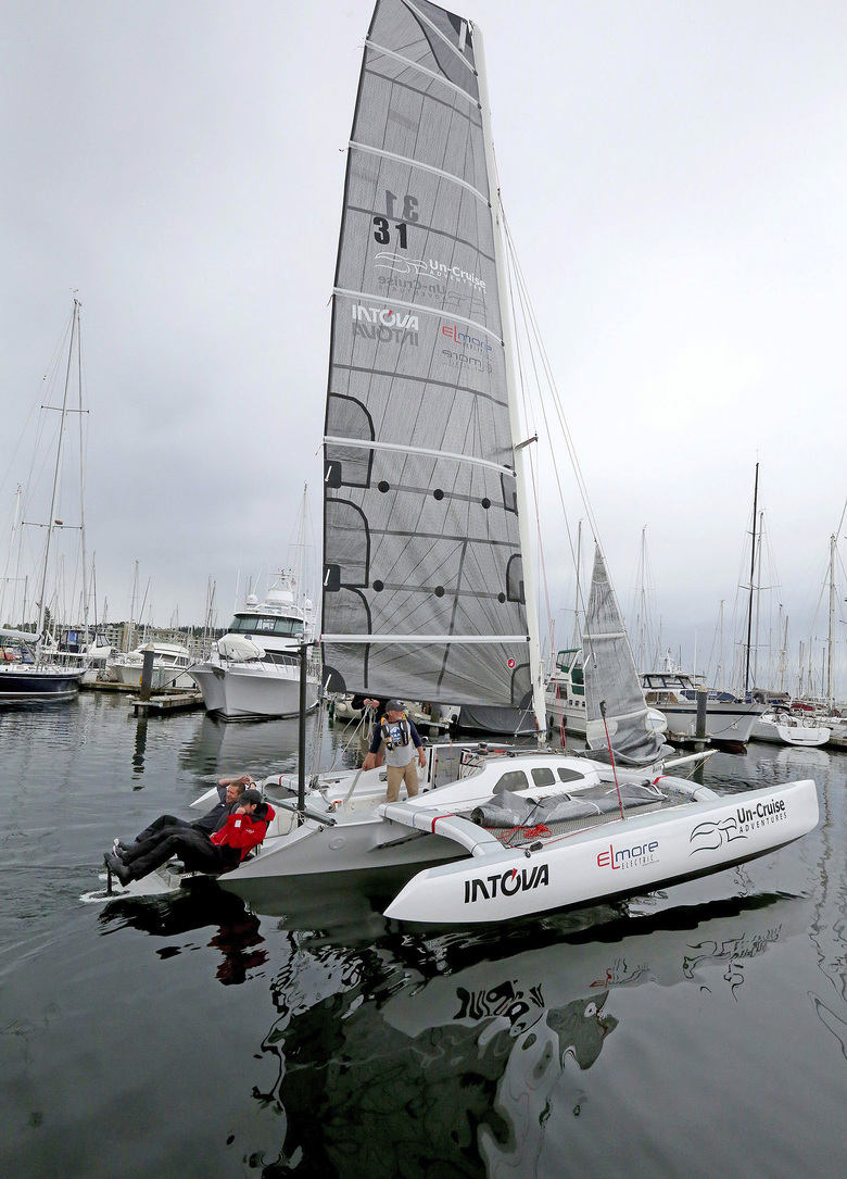 Dan Blanchard's trimaran goes for a test run for Race to Alaska at Shilshole Bay Marina. Using human power at the stern are crew members Graeme Esarey, left, and Dave Niffin.  (Greg Gilbert/The Seattle Times)