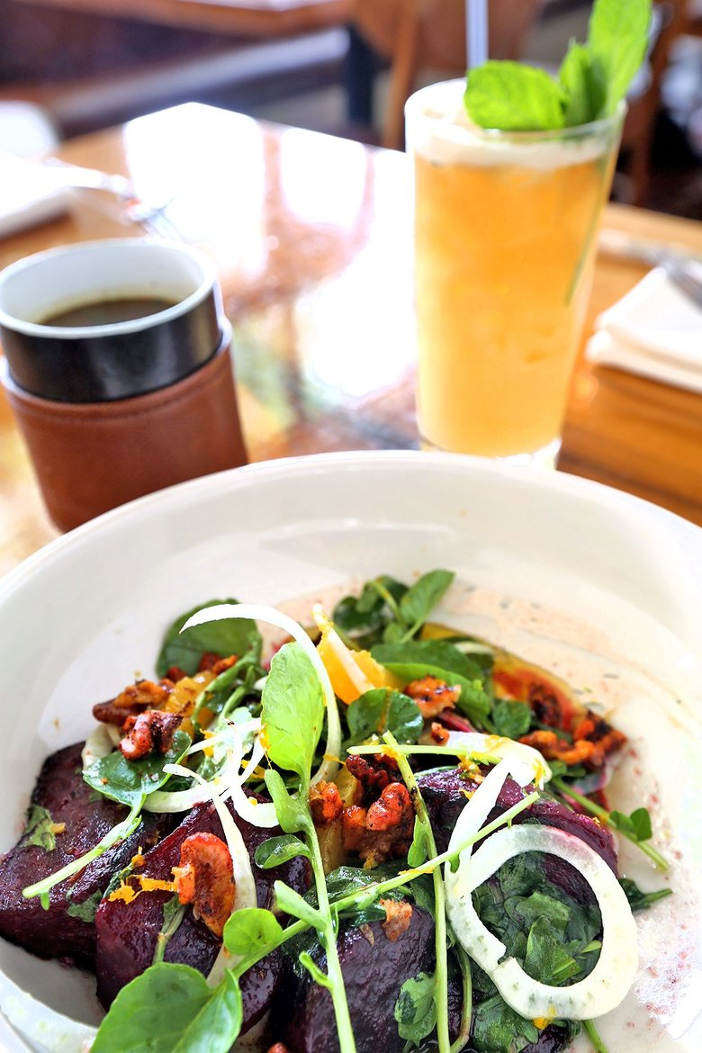 Hot Beets are served with a mug of bone broth at Eve, in Fremont. The drink is their Fremont Paralysis, with aquavit, pineapple, orange, lemon, mint, almond milk and a dark rum float. (Greg Gilbert/The Seattle Times)