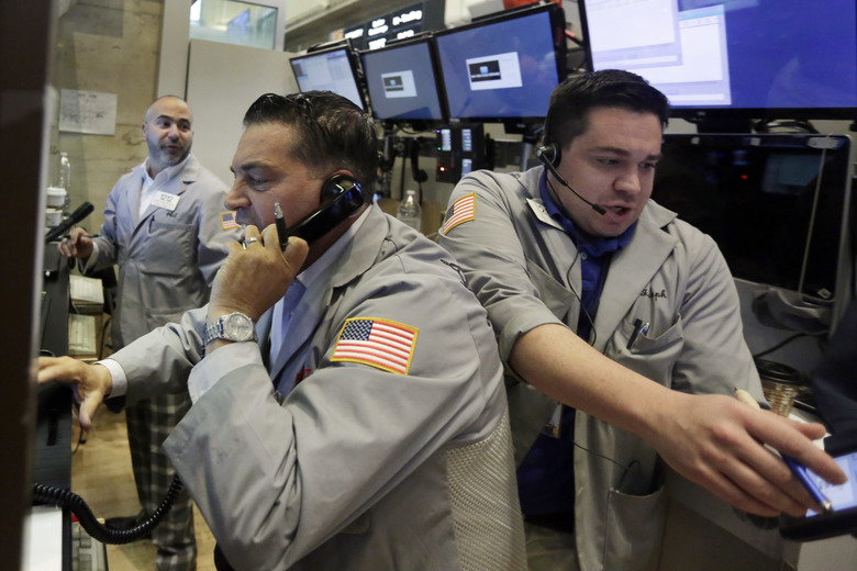 Traders Jonathan Mueller, center, and Joseph Lawler, right, work on the floor of the New York Stock Exchange, Friday, June 24, 2016. U.S. stocks are plunging in early trading after Britons voted to leave the European Union. (AP Photo/Richard Drew)