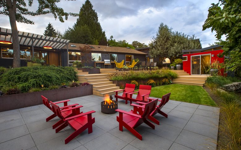 Ryan Smith and Ahna Holder's contemporary garden is all about outdoor living. Red Adirondack chairs from Loll Designs are grouped around a firepit on the lower terrace. The planting beds are built of COR-TEN steel. In the background are butterfly chairs, the beehive-shaped pizza oven and a Modern-Shed red playhouse. (Mike Siegel/The Seattle Times)