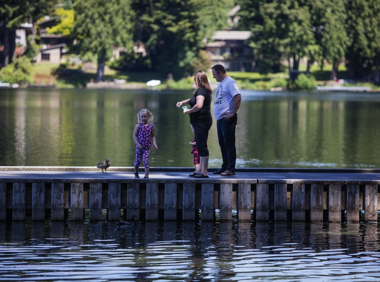 A family enjoys the dock at Pine Lake in Sammamish.  (Steve Ringman/The Seattle Times)