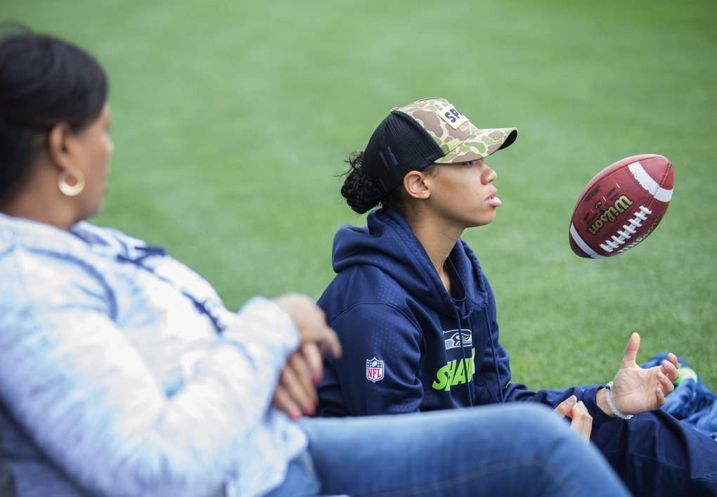 Russell Wilson's sister Anna Wilson, who will play basketball for Stanford in the fall, twirls a football as she watches with their mother Tammy Wilson.  (Lindsey Wasson / The Seattle Times)