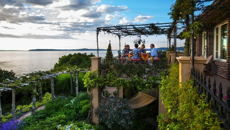 Roger and Candace BelAir built two decks for outdoor dining along the back of their home. Vines climb up to lace the pergola in flower and leaf, and a chandelier lights up the night. (Mike Siegel/The Seattle Times)