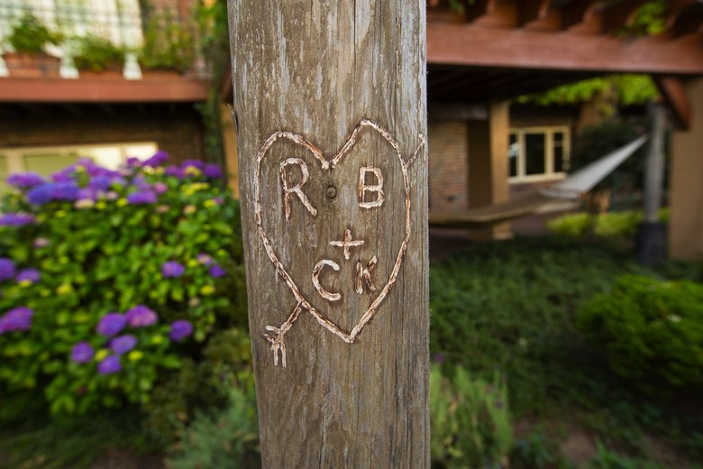 """The couple's initials carved into one of the driftwood arbor posts emphasize the romantic feel of the garden. The arbor also is embellished with dozens of """"love locks,"""" a gift from Roger to Candace inspired by locks they'd seen on a bridge in Paris. (Mike Siegel/The Seattle Times)"""