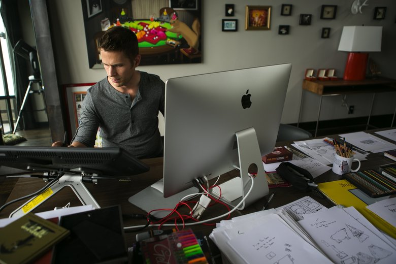 Matthew Inman works up to 12 hours a day at his home office in Seattle. (Bettina Hansen/The Seattle Times)