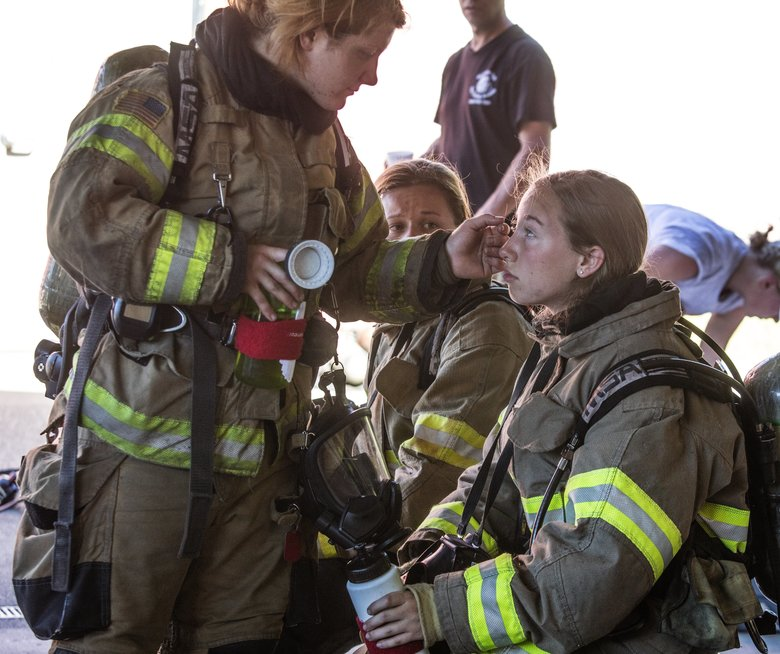 Between firefighting sessions, Kaitlyn Little, 17, of Denver takes a break as career firefighter and volunteer Jessica Johnson of Lacey wipes soot off Little's face.  (Steve Ringman/The Seattle Times)