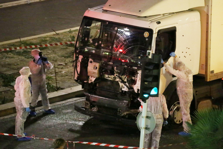 Authorities investigate a truck after it plowed through Bastille Day revelers in the French resort city of Nice on Thursday night, killing scores of people. (Sasha Goldsmith via AP)