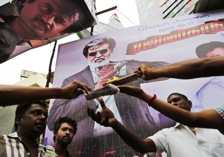 "Fans of Indian superstar Rajinikanth offer prayers outside a cinema before the screening of ""Kabali"" in Chennai, India, Friday, July 22, 2016. Hundreds of thousands of fans of Indian superstar Rajinikanth are thronging cinemas across the country to catch the premiere of his latest film, ""Kabali"". Sixty-five-year-old Rajinikanth is one of India's most popular star and counts millions of fans who speak the Tamil language and even those who don't. (AP Photo/Aijaz Rahi)"