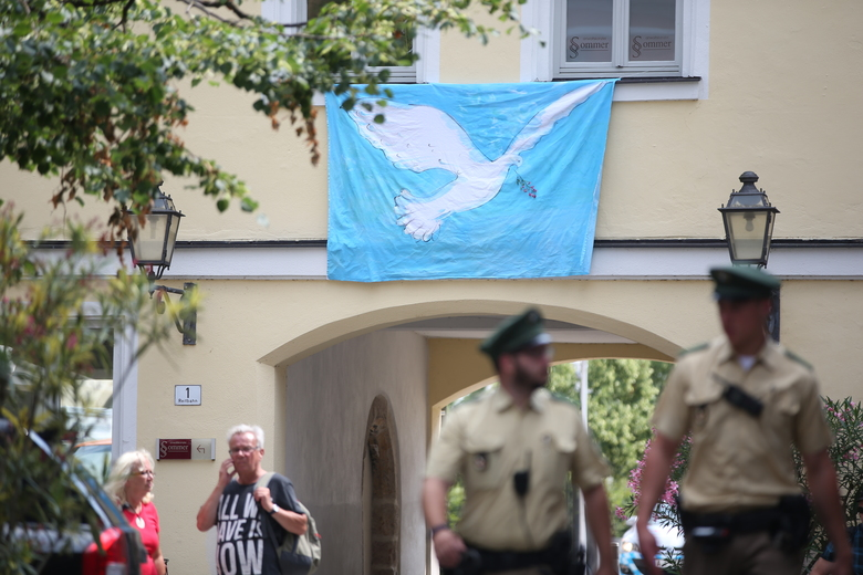 GERMANY OUT – Police officers walk past a wall with a peace dove on a banner at the site of the attack in Ansbach, Germany,Tuesday July 26, 2016.  In the most recent attack, a 27-year-old Syrian asylum-seeker set off a backpack laden with explosives and shrapnel Sunday night after being refused entry to a crowded music festival in the Bavarian city of Ansbach, killing himself and wounding 15 people.  (Daniel Karmann/dpa via AP)