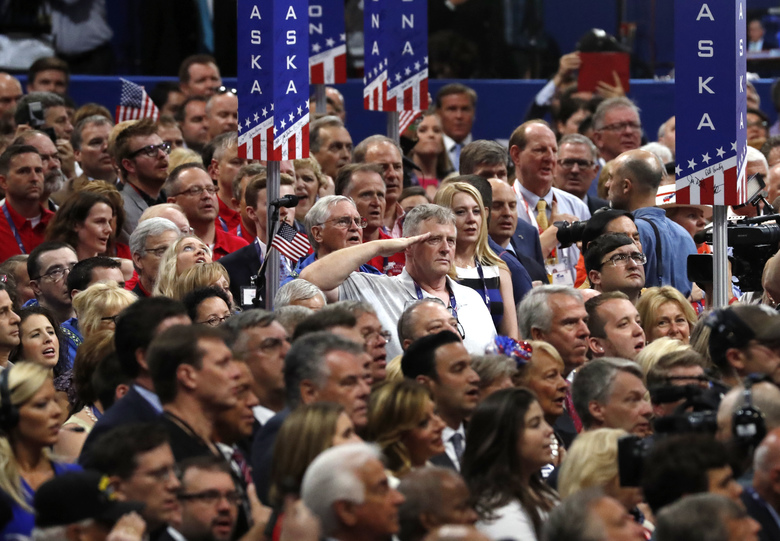 A man salutes during the singing of the National Anthem on the final day of the Republican National Convention in Cleveland, Thursday, July 21, 2016. (AP Photo/Paul Sancya)