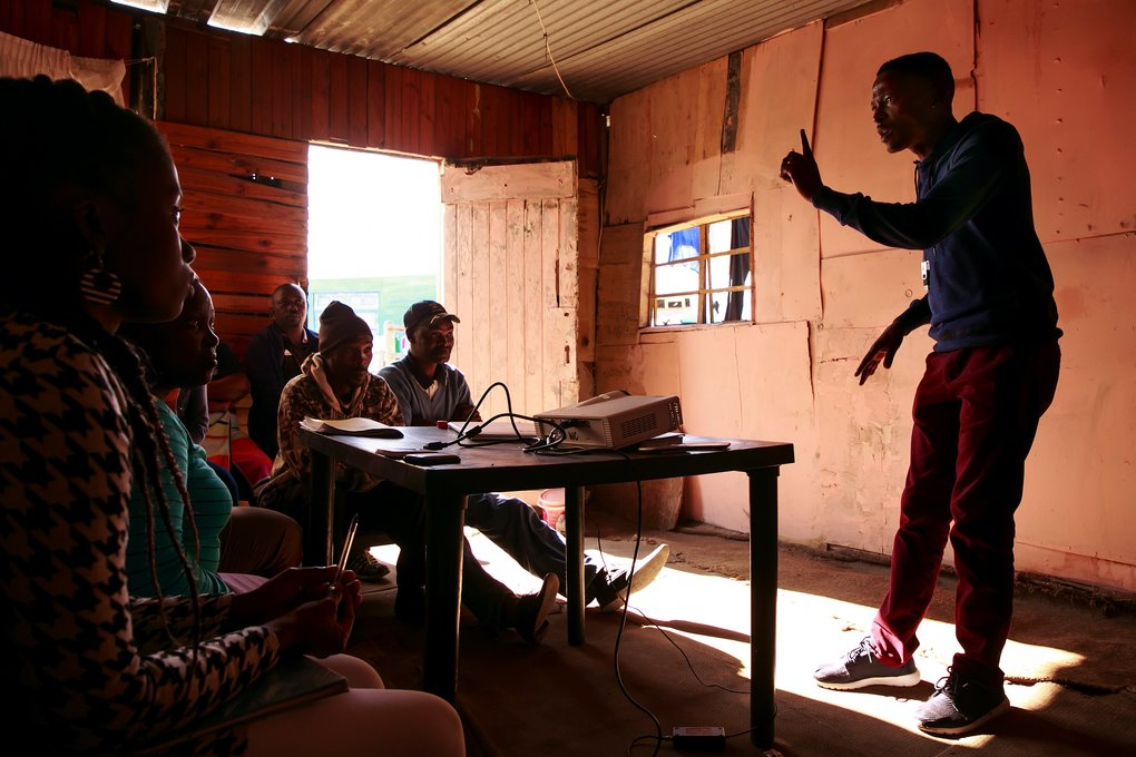 Andile Madondile gives a science-heavy talk on HIV in a shack in Khayelitsha, a township outside Cape Town. An HIV activist, Madondile is trying to educate his neighbors and encourage sometimes-fearful South Africans to sign up for a clinical trial led, in part, by the Fred Hutchinson Cancer Research Center. (Erika Schultz/The Seattle Times)